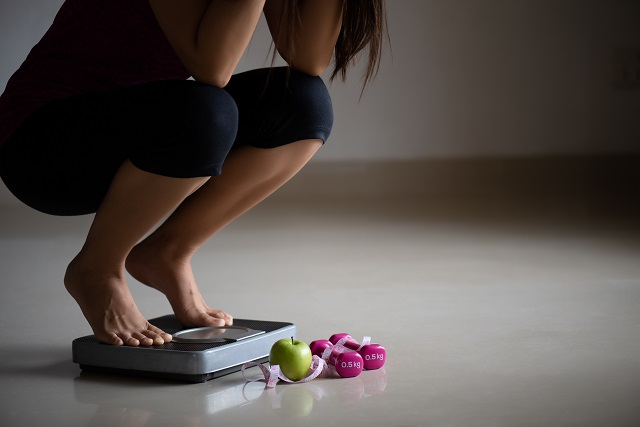 yscClose up upset female leg stepping on weigh scales with measurin