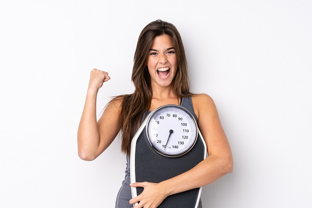 yscTeenager Brazilian girl holding a scale over isolated white background with weighing machine and doing victory gesture