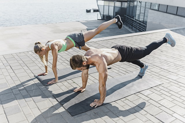 Fit fitness woman and man doing fitness exercises outdoors at city