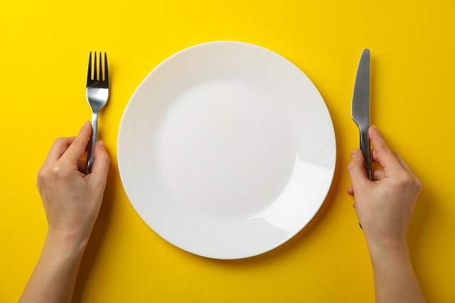 Female hands hold fork and knife on yellow background with plate
