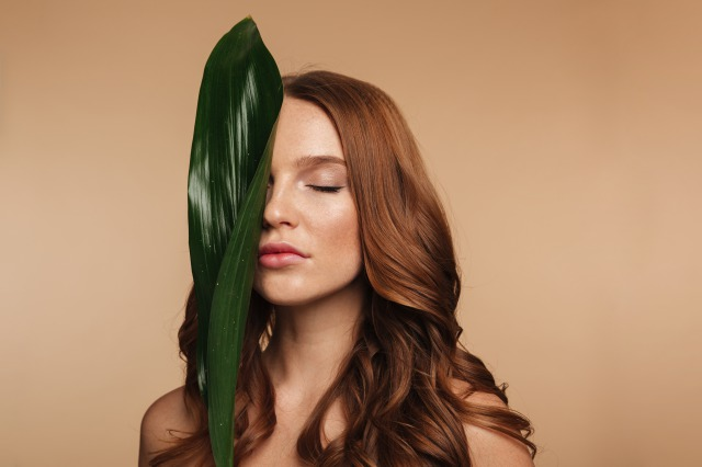 ysc-beauty-portrait-of-sensual-ginger-woman-with-long-hair-posing-with-green-leaf