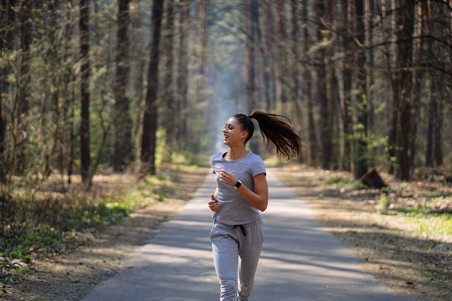 Beautiful young woman running in green park