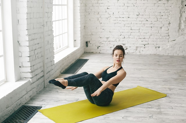 Exhausted young European woman performing boat asana while practicing yoga indoors. Brunette girl sitting on green mat, doing navasana pose with back and legs lifted and arms extended forward