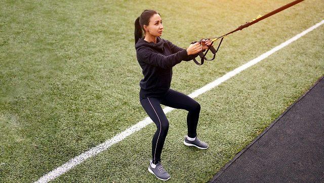 Girl athlete training using trx sportground Mixed race young adult woman workout  suspension system Healthy lifestyle Stretching outdoors playground. Make your body machine