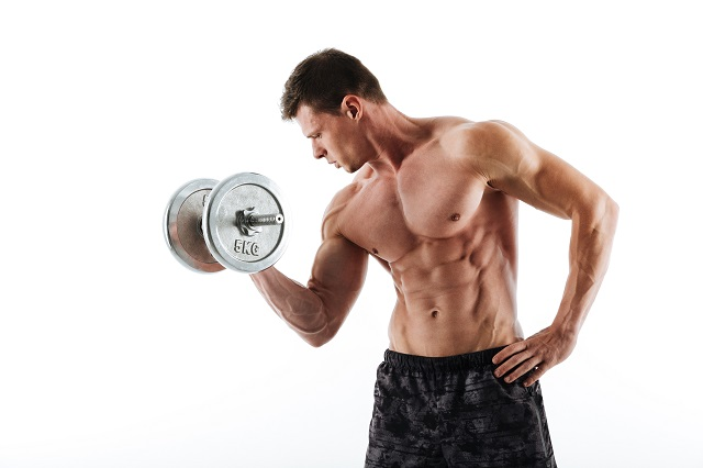 Topless young athletic man working out with heavy dumbbell, isolated over white background