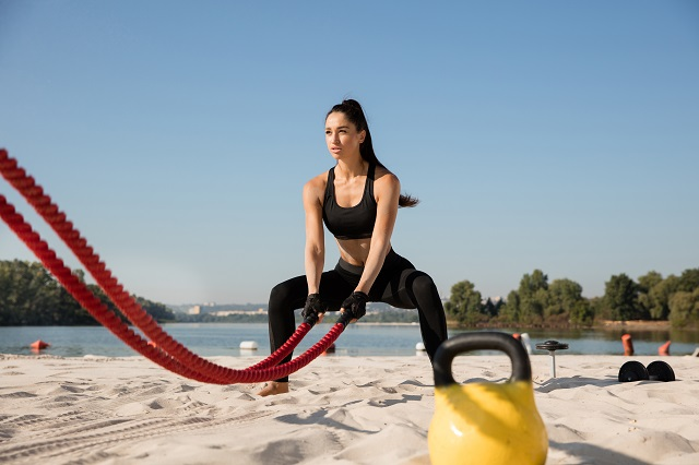 Young healthy woman doing exercise with the ropes at the beach. Single caucasian female model practicing at the river side in sunny day. Concept of healthy lifestyle, sport, fitness, bodybuilding.